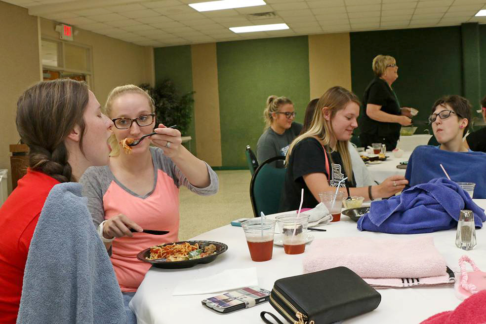 PRACTICING SKILLS Paris Junior College students in the licensed vocational nursing program recently practiced the art of feeding patients. They took turns in role-playing, simulating impairment in patients. Shown from left are Sulphur Springs students Michala Davis and Kasie Brantley, Karli Emmons of Cumby, and Mysti Dooley of Greenville.