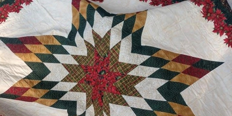 "Christmas Star Quilt made by: Cara Duncan. Full size 79"" x 79"". Dark green back, front has Christmas Star trimmed with Poinsettias - Donated by Bill & Beverley Owens"